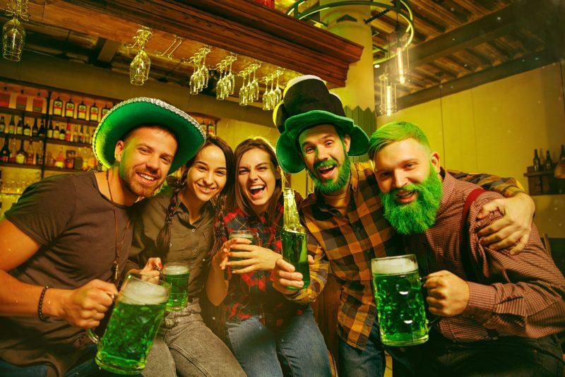 Amigos celebrando a cultura irlandesa tomando cerveja verde em um pub.