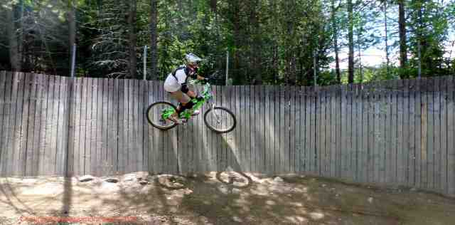boy riding a wooden wall on a downhill bike at trestle bike park in winter park colorado