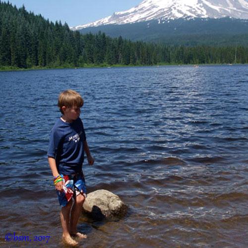 a young boy wading in trillium lake near mount hood oregon