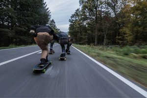 photo of two people longboarding down a mountain