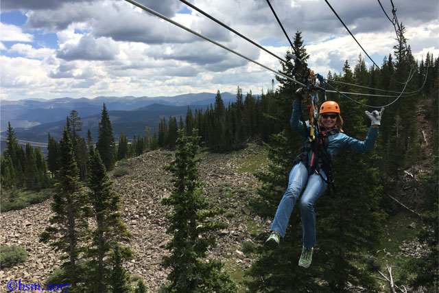 hanging from the zip line on the Expedition zip line tour at breckenridge colorado