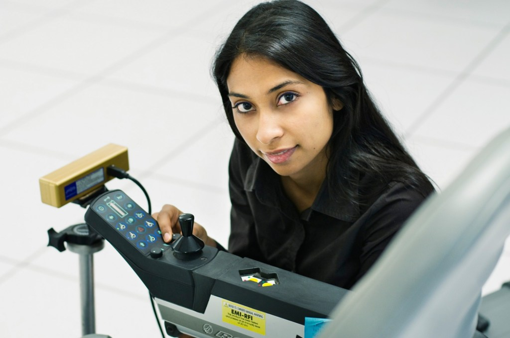 Photo of Pooja Viswanathan beside the joystick of a wheelchair