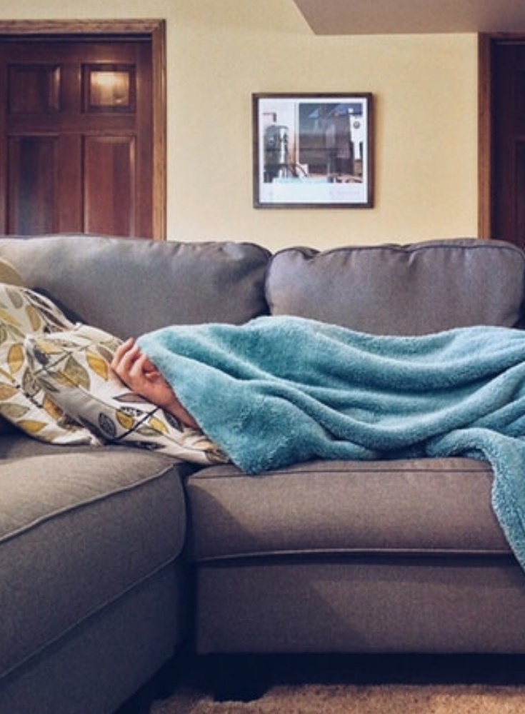 man on couch laying down under covers