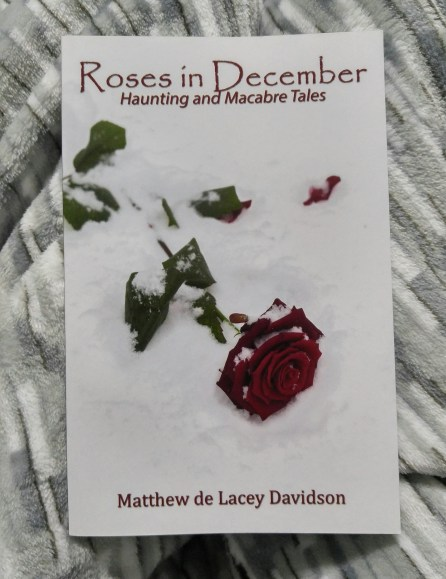 The book Roses in December lying on a blanket
