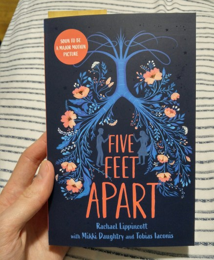 A hand holding the book Five Feet Apart
