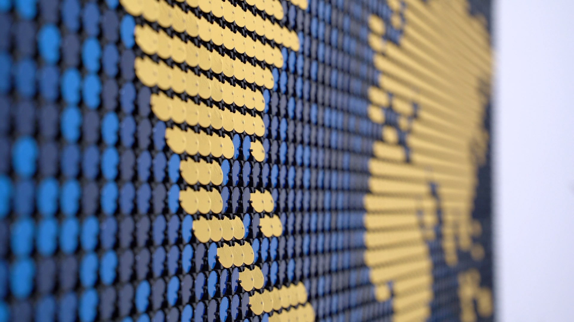 Close up of blue and gold Flip-Discs artwork called Seismic Echo, showing a map with real-time seismic activity overlaid. Created by BREAKFAST.