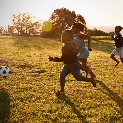 group of children running after soccer ball