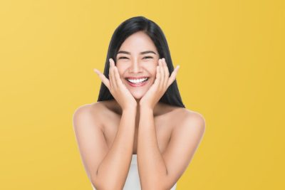 IRF-skin-tightening-Young-woman-touching-her-face-in-soft-yellow-background