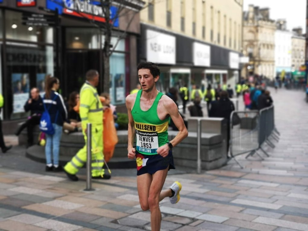 A fast young male runner in a green vest looking very laid back running through the city centre