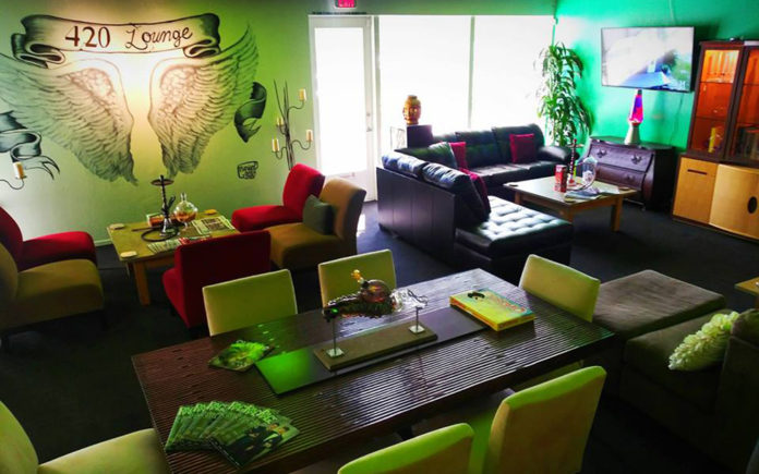 A cannabis friendly lounge painted in green and with comfortable couches.