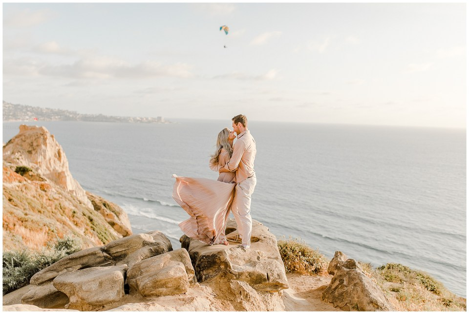 man and woman standing on a rock during their engagement pictures in la jolla, california