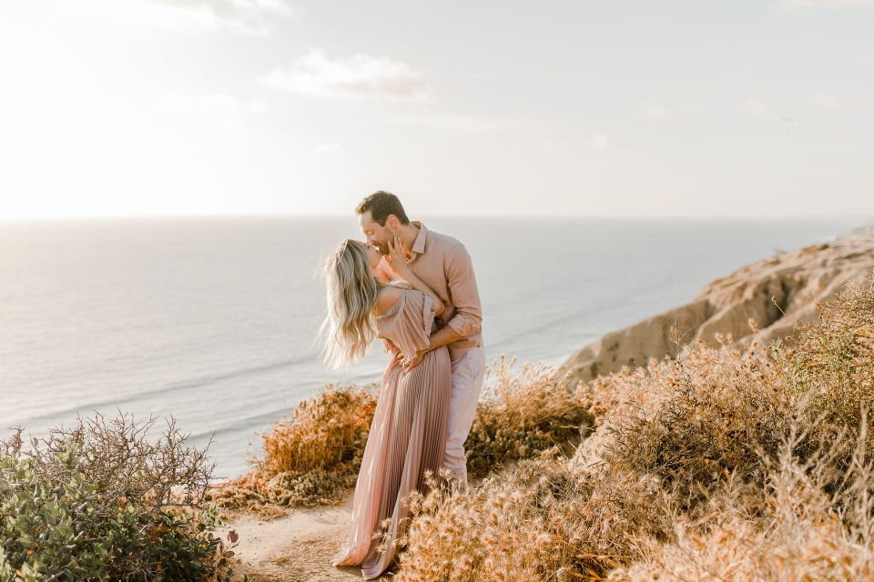 couple kissing by the sunset during their torrey pines gliderport engagement session