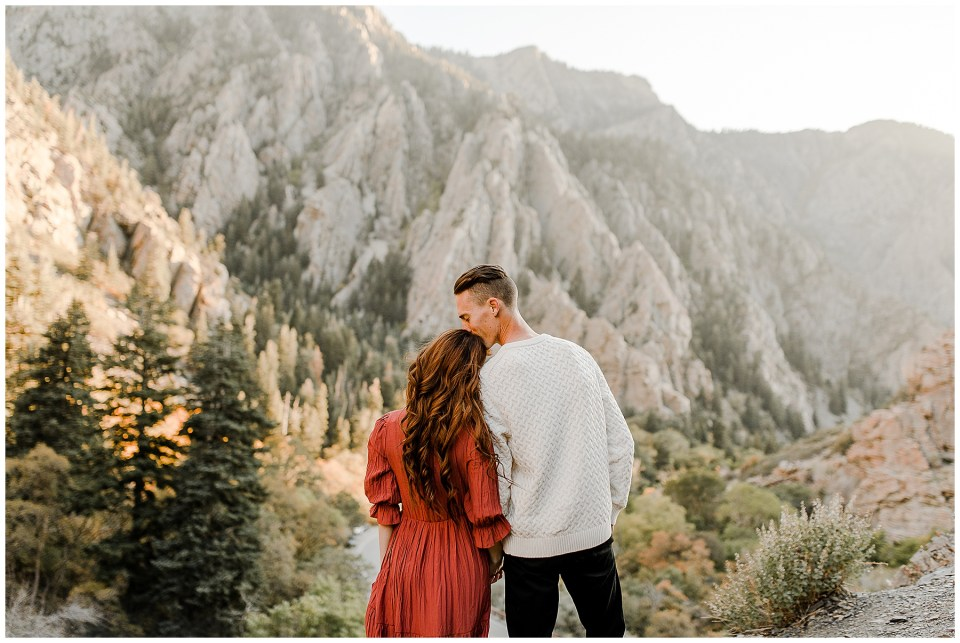 man kisses his fiance on the head while they look at the mountains during sunset on their Big Cottonwood Canyon Engagement Session