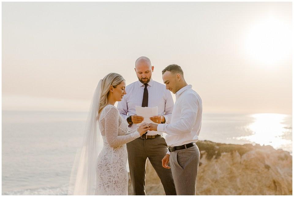 bride and groom exchange rings during their el matador beach elopement