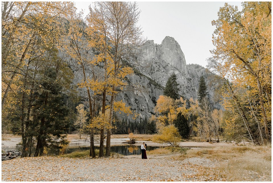 bride and groom kissing with a beautiful fall colored backdrop during their adventurous yosemite engagement session