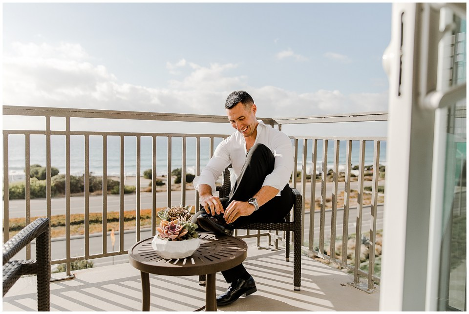 groom getting ready at cape rey carlsbad during their Adventurous Beach Elopement in Carlsbad, California