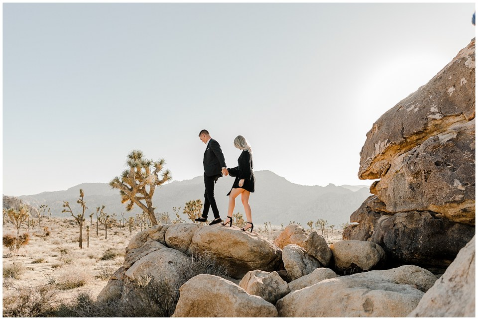 man and woman climbing on a rock during their joshua Tree National Park Engagement Photos