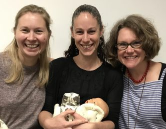 Claire Reading, Emma Spillane and Shawn Walker, three women smiling at the camera. Emma is stood in the middle with a small practice baby.