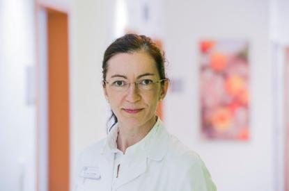 Portrait shot of a brunette woman wearing glasses and in a white doctors uniform Dr Anke Reitter a member of the International Breech Birth Network