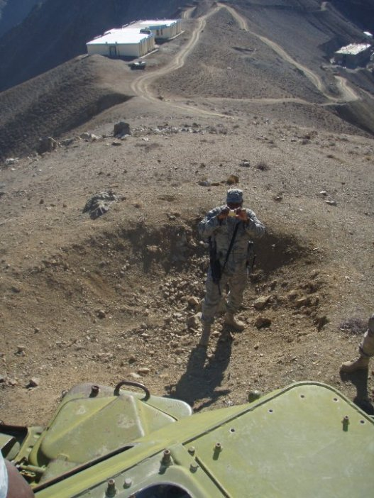 Taken from atop the vehicle, you see one of our team members standing in a bomb crater. Behind him and to the right you can see the 16 room school under construction.