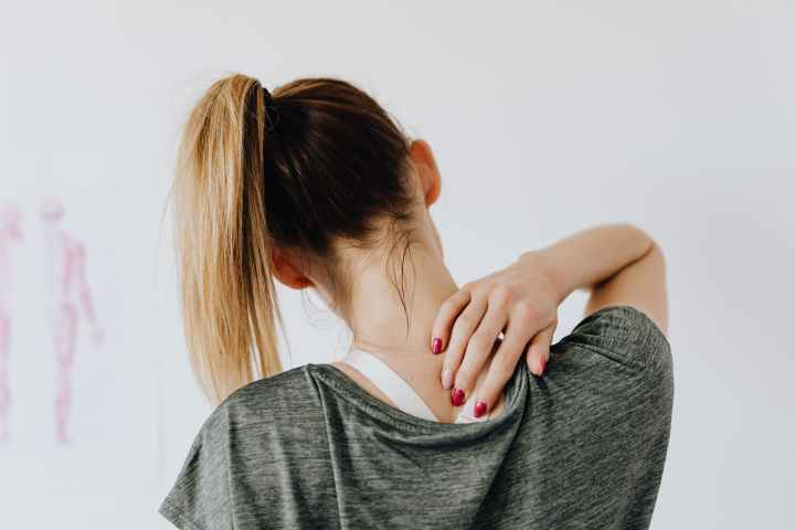 unrecognizable woman showing pain spot on back in doctor office