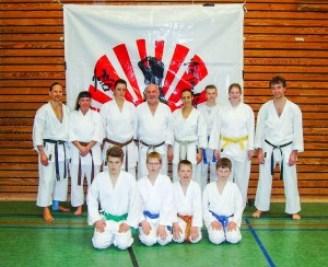 Karatefreunde vom Delmenhorster TV beim Lehrgang im BKV vor dem Vereinslogo des Ausrichterdojos SKIP-Karate-Dojo Bremen e.V.