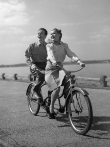 1950s-happy-couple-man-woman-riding-tandem-bike-bicycle-built-for-2