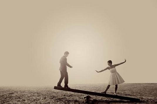 couple balancing on beam sepia