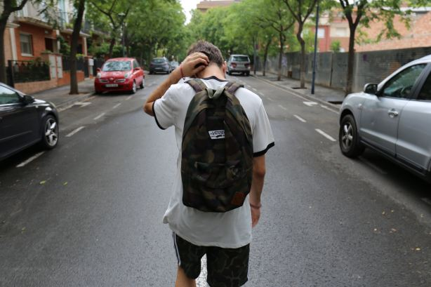 boy walking away with backpack