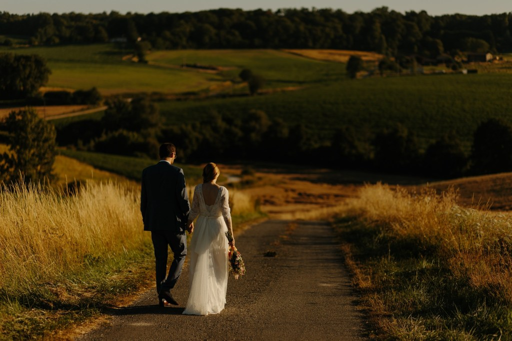bride and groom walking on road