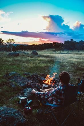 boy by fire camping