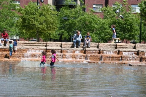 Grandpa and Jamison watch kids playing in the water at Jamison Square
