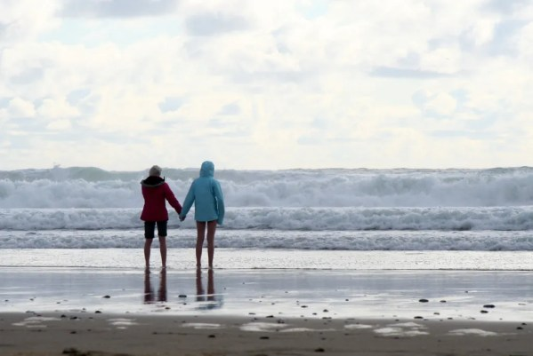 Two girls hold hands while waiting for a wave