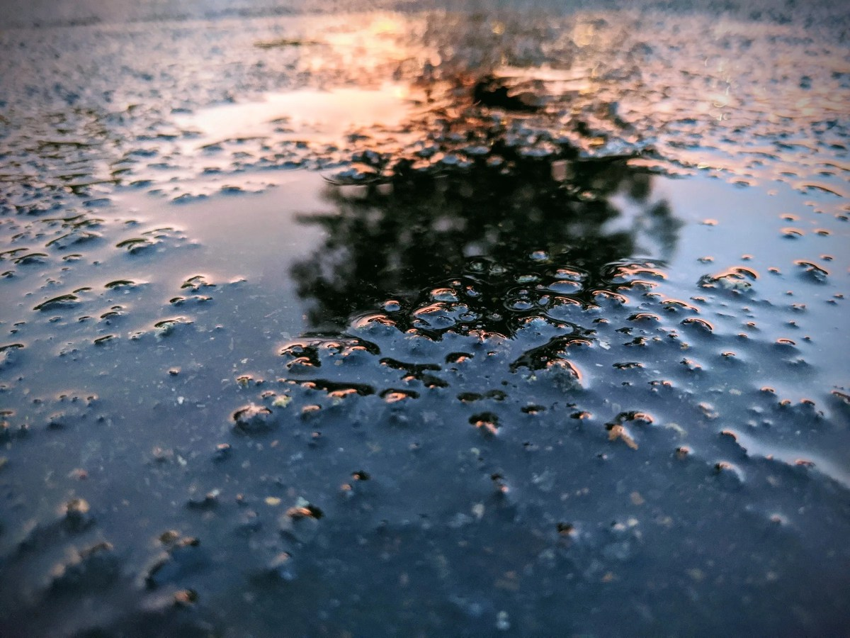 Sunset reflected in a puddles on the road