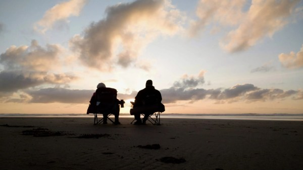 a couple sits and contemplates the sunset at Canon Beach