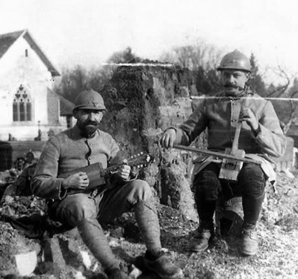 Soldier playing a Cigar Box mandolin and what looks like a mini-cello.