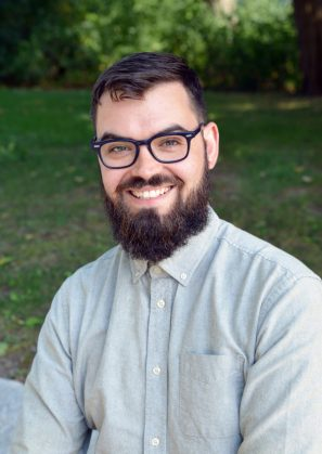 Photo of Brent, who smiles and looks towards the viewer. He is bearded, has blue glasses, and wears a button-down shirt. The camera focuses on him in the foreground, and the green lawn in the background is out of focus. © Gagne Photo. Used with permission.
