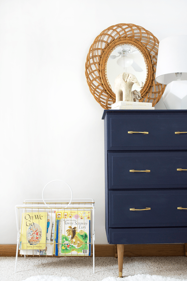 A vintage magazine rack gets turned into a book holder for a modern boho nursery!
