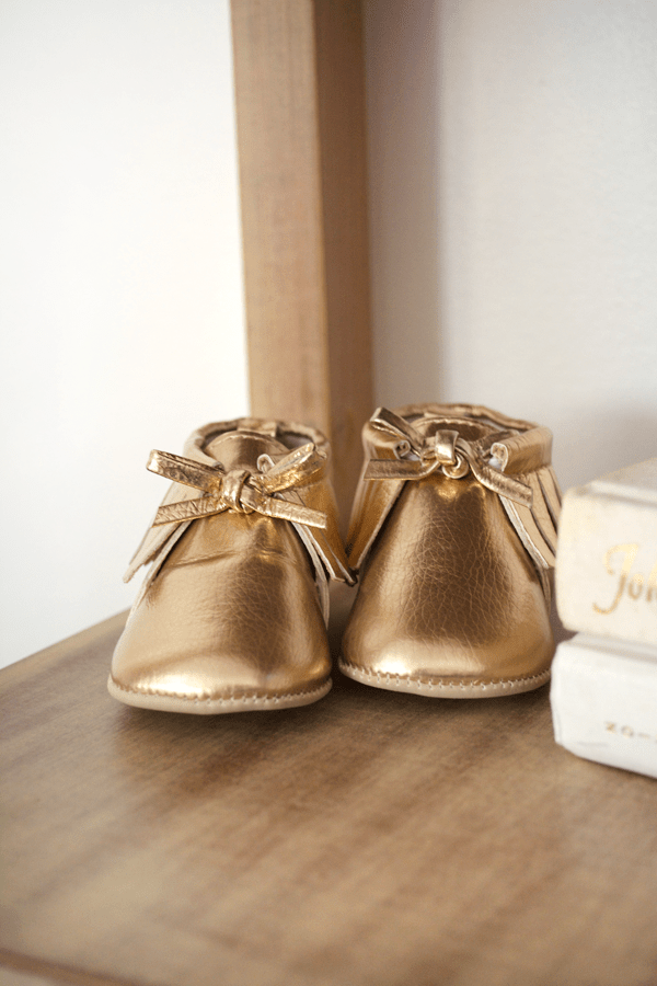 gold baby moccasins in nursery