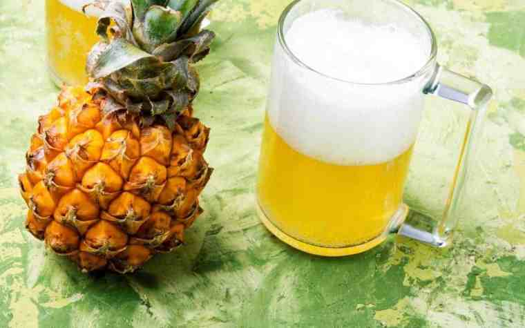 Whole pineapple fruit and a mug of pale pineapple beer