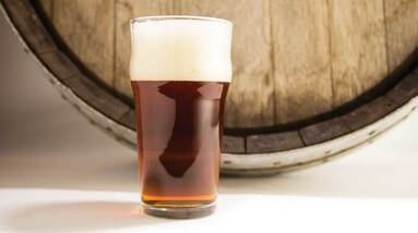 A glass of amber beer in front of a wooden cask