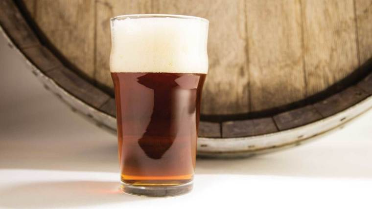 A glass of amber color beer in front of a  wooden barrel.