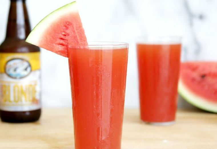 A glass of watermelon beer decorated with a watermelon wedge.