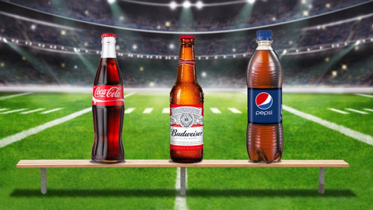 A bottle of Coke, Budweiser and a Pepsi on a bench in the middle of a football field.