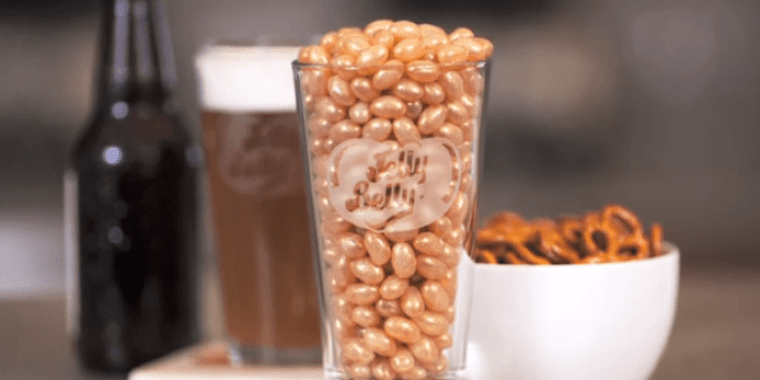A beer glass filled with beer flavored jelly beans and a bowl of salty pretzels with a glass of beer and a beer bottle in the back.