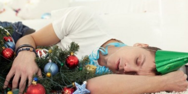 A person sleeping on the floor with a party hat and hugging a decorated Christmas tree.