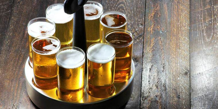 A stainless steel tray filled with glasses of Kolsch beer on a wooden table.