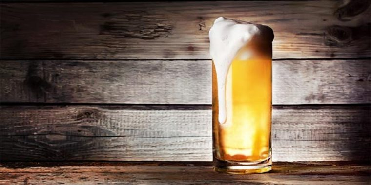 A glass of Kolsch beer in front of a wooden background.
