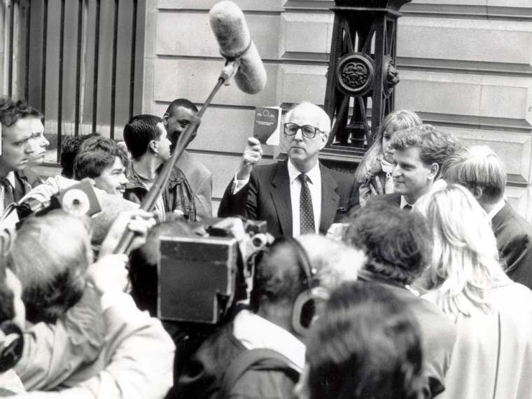 Ernest Saunders CEO of Guinness company surrounded by news reporters.