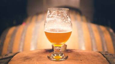 A half full glass of sour beer standing on a wooden barrel.